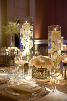great picture of submerged orchids and floating votives. With the addition of a shorter vase filled with one type of floral. Square and cylinder both look great!