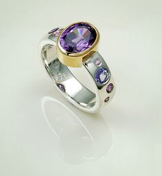Ring: Amethyst set in 9ct gold with flush set sapphires, tanzanites and amethysts in the sterling silver band.