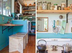 Cozinha com paredes em tinta turquesa e estantes em madeira no lugar dos armários. Bancos com tratamento em envelhecido.