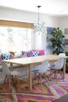 idée déco salle à manger - tapis bariolé, coussins décoratifs en rose et bleu et tableaux en bleu et à motifs divers