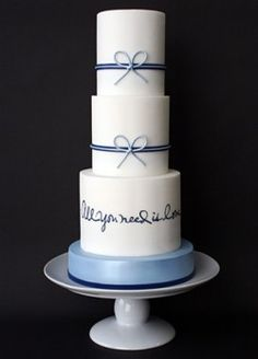 'All You Need Is Love' Wedding Cake. Love the cake stand. It colorful but matches the blue of the ribbon and words and looks so apart of the cake.