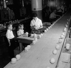c. 1955 Children watch a worker painting doll's heads at a factory in Long Island. IMAGE: ORLANDO /THREE LIONS/GETTY IMAGES