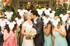 The bride and groom kiss with wedding guests' faces hidden by Mickey Mouse programs for a Disneyland wedding.