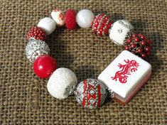 This oriental Mahjong bracelet is made with a red dragon Mahjong tile in the center. The tile is a white on the front. The back is a glitter pink. There is also a middle layer of clear in the middle. The dragon is a bright red on the white background.. The Beads are red and white Jesse
