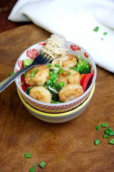 GInger shrimp with Rice Noodles 1 lb uncooked shrimp, tails removed 3 tablespoons soy sauce 2 tablespoons fresh ginger, minced  1 tablespoon fish sauce 2 teaspoon sesame oil 2 teaspoons rice wine vinegar 2 teaspoons sugar 1 teaspoon sriracha 2 tablespoons olive oil 4 cloves garlic 1 head of broccoli (steamed) 1/2 red pepper (steamed) 1/2 green pepper (steamed) 1 (12 ounce) package rice noodles scallions for garnish