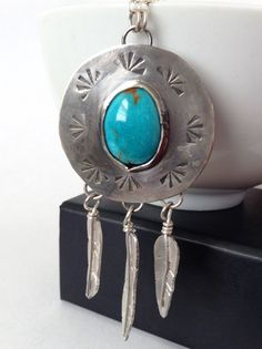 """Hand stamped turquoise tribal shield necklace with feathers. Gorgeous turquoise necklace with hand crafted feather dangles and a hand stamped border. The pendant measures 1"""" (2.5 cm) across and is abo"""
