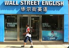 A Chinese man walks past a popular English language school in downtown Beijing on June 9, 2017. Learning English has been at the forefront…