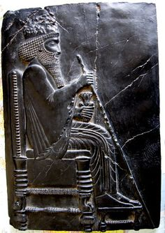Later Babylonian & Assyrian. Seated King with scepter.  Note the chair has a relatively high back and the legs have stretchers between them.  The legs have also been turned, which indicates they had tools available for use.  The figures hair is decorated, his feet rest on a stool and in his left had is some kind of container.