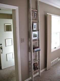 ladder used for hanging photo frames.....I want to do this since I have NOTHING on my walls because they are plaster and I am afraid they will come tumbling down if I try to put any sort of hole through it.  Great solution....now to find a ladder!