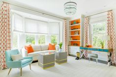This gorgeous blue and orange home office features a white sofa accented with orange pillows and placed beneath bay window covered in white roman shades complemented with white and orange curtains. Orange Curtains, Orange Pillows, Orange Sofa, Blue Home Offices, Blue Shelves, Interior Design Masters, White Office, Orange Office, Shingle Style Homes