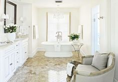 fabulous white bathroom with stunning glossy stone floor and linen chair