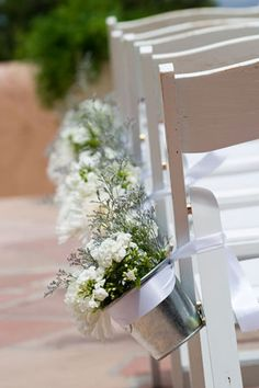 flower filled buckets tied to chairs  @Jennie Mathews I have a whole bunch of white ones if you want to use.