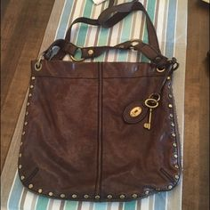 "Brown Studded Hobo Bag by Fossil  Super soft rich brown leather with brass/gold studs around edge - has 2 different length straps so you can use it numerous ways ✨ crossbody / shoulder / measures 14x13 with a 19"" shoulder drop strap and shorter handle strap. LOVE THIS BAG!! ✨ also has inner zip pockets and other side has 2 pockets for phone etc - awesome!!  Fossil Bags Crossbody Bags"