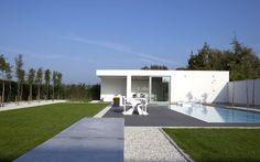 Minimalistisch poolhouse in witte crépi in strakke tuin. Modern poolhouse met keuken, badkamer en sauna.