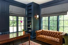 Blue paneled den boasts a tobacco leather chesterfield sofa placed under windows dressed in a platinum gray silk roman shade.