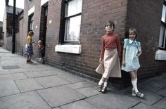 Girls smile on a street corner in Manchester, England, c. 1960s. Photograph by John Bulmer.
