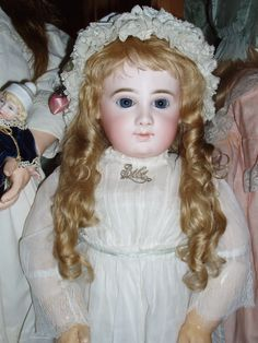 Hand-wefted mohair wig with tails on a beautiful antique French Jumeau Bebe.