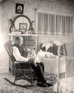 Man Holding Baby - what I love most oabout vintage photos is the details....what's on the dresser, the linens, wallpaper, their clothes, etc.  All the tiny things