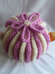 hand knitted tea cosy/cosie pink and cream with flower to top and button to center of flower weaved at the back to keep your tea pot hot! machine wash at 40 will fit a medium pot(4-6)cups 25%wool 75% acrylic £20.50
