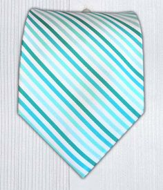 """Polo Stripes - Aquas (#11278). White textured silk alternating with four shades of aqua (teal, tiffany blue and turquoise). Wear only a white shirt but still look like a total stud. Handmade of 100% Woven Silk. $15.00for Regular Length (58"""" x 3 ½""""); 20.00for Extra Length (63"""" x 3 ¾""""); 15.00for Boys Tie (48"""" x 2 ¾"""")."""