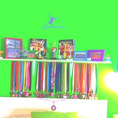 If you need a place to hang medals...place a shelf on the wall to gather trophies, etc...and get command hooks to place underneath the shelf to display the medals!