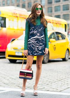 A printed shift dress is worn with a green turtleneck