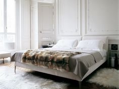 Bedroom Bliss. White walls, and white bedding with a fur throw.