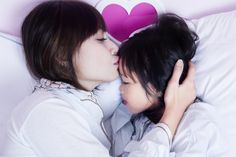 Portrait of young mother kissing her child forehead while lying on the bed
