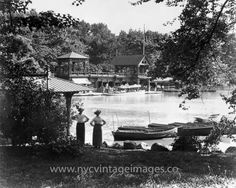 A summer day in 1914.  Two women stand on the edge of the lake in Central Park, arms akimbo, looking across at the boathouse.  This edifice was designed by Calvert Vaux shortly after the completion of the park.  It burned to the ground in1950 and was replaced by the current Loeb Boathouse.