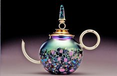 "Teapot of blown and iridized glass with lid, handle and spout of 24 karat gold over sterling silver. Lid holds a matrix turquoise. 7"" tall"