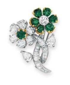 A DIAMOND AND EMERALD BROOCH, BY GRAFF   Designed as two circular and pear-shaped diamond and emerald flower blossoms with contrasting pistils, to the baguette-cut diamond stems with pear-shaped diamond leaves, mounted in gold and platinum, with pendant hoop for suspension  Signed Graff, no. 3655