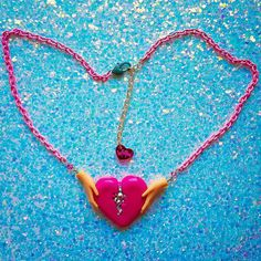Broken Heart Necklace - Made to order. Ready in 5 business days.   Inspired by the traditional Irish claddagh, I hand cast this epoxy resin broken heart pendant and painted it bright magenta then filled the center with two sizes of iridescent Swarovski crystals. The hands are genuine doll parts that I personally cut and attach. The pendant is suspended from pale pink vintage enamel chain. Closes with a lobster clasp and extender chain.    ♡ Size: Necklace measures 16 inches but can be…