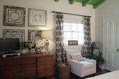 O teto verde, as paredes brancas e mobilias, cortinados pretos e brancos, chão castanho, plantas