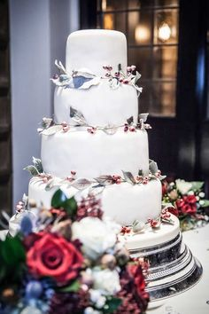 www.sylviaskitchen.co.uk Four tier wedding cake at The Star, Alfriston, East Sussex.  Iced in an ivory fondant base and decorated with wreaths to each tier of wired sugar foliage and deep red wired sugar berries.  Cake  finished with a light frosting effect Image FitzGerald Photographic