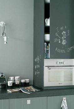 Grijze keuken met dik blad en een zuil op het blad met een kastje en de oven.