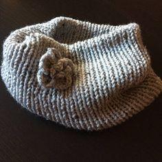 Questo scaldacollo in maglia è decorato con un fiore realizzato ad uncinetto. È realizzato artigianalmente per cui eventuali imperfezioni sono da ritenere pregi che lo rendono unico.
