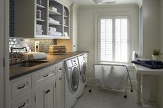 stone-colored tile and counters in this laundry room - insides of the shelves are painted a nice gray - cabinet underlighting