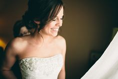 Happy bride getting ready in the window light for a Normandy Farm Wedding.