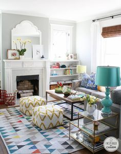 A colorful living room: geometric print rug, grey couch, big mirror, turquoise lamp, lovely coffee tables