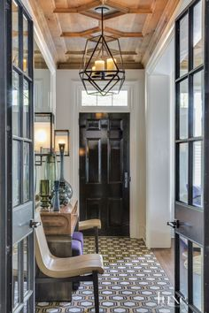 The custom ceiling by Duncan Cabinetry of Wrightsville, Pennsylvania, provides traditional style while echoing the entry's tile pattern. A Kevin Reilly pendant from Holly Hunt and O'Lampia Studio sconces illuminate Siren side chairs (also from Holly Hunt) and a custom steel-and-walnut-topped console.