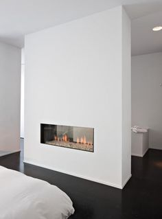 Double sided wall mounted fireplace in the bathroom.   See-Through ...