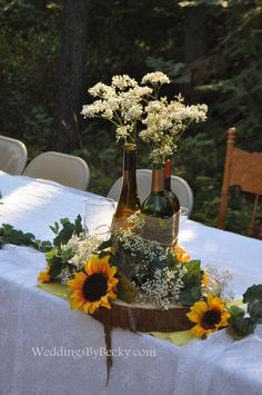 Wine bottles tied together with burlap- babies breath and sunflowers accent the head table.: