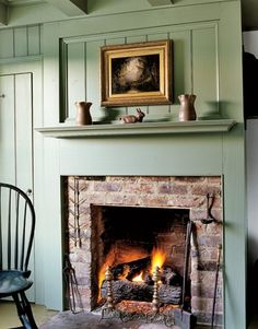 Build a mantel around brick fireplace. sage green raised panel wall reveals a simple brick fireplace in this home. Antique pottery is displayed on the mantel. Country Fireplace, Fireplace Mantle, Fireplace Surrounds, Fireplace Design, Cottage Fireplace, Fireplace Ideas, Mantel Ideas, Farmhouse Fireplace, Wooden Fireplace Surround