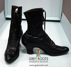 A pair of ladies', black, high-topped, Queen-heeled, lace-up boots circa 1917. The exterior is patent leather and the interior is cotton. They are made by Hanan & Son. Grey Roots Museum & Archives Collection.