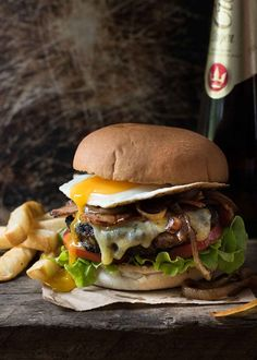 Fully loaded Hamburger with bacon and egg, with a side of chips and beer, ready to be eaten