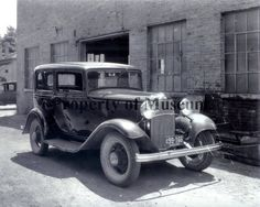 Photograph of 1932 two door Model A Ford at corner of Court & Locust Streets, Urbana, OH.  (The Champaign County Historical Museum)