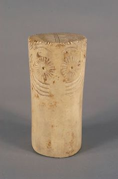 ÍDOLO DE MORÓN DE LA FRONTERA (SEVILLA) corresponde a un periodo Calcolítico (3000-2100 a.C.). Con una altura de 14,5 cm. y esculpido en mármol, presenta decoración incisa, representando un rostro con ojos en hueco, cejas y cuatro líneas de tatuaje facial, que se prolongan en la parte posterior. Se corresponde con un tipo propio de la Península Ibérica, cuya característica más común es su forma cilíndrica. Pueden ser lisos o con una llamativa decoración.