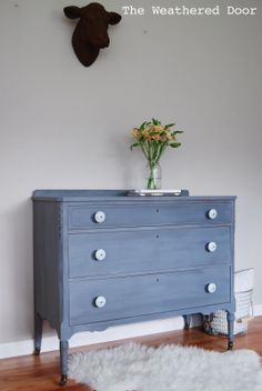 The Weathered Door: A grey-blue-purple dresser with soft blue knobs