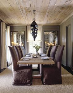Natural wood ceiling, dark walls, antique mirrors and oyster color drapes
