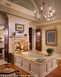 The traditional style in this luxury master bathroom is gorgeous. Mahogany doors. White trim. Marble and wood tub surround. Chandelier over bathtub.